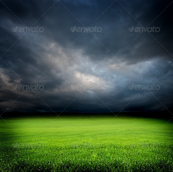 dark cloudy sky and green grass meadow - Stock Photo - Images