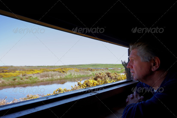 A man bird watching over a lake - Stock Photo - Images