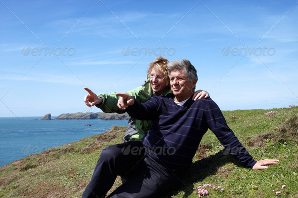 A mature couple sitting on the coastal path - Stock Photo - Images
