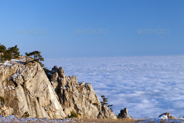 Sunlit cliffs and sea in clouds - Stock Photo - Images