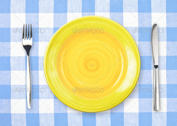 Knife, yellow plate and fork on yellow checked tablecloth - Stock Photo - Images
