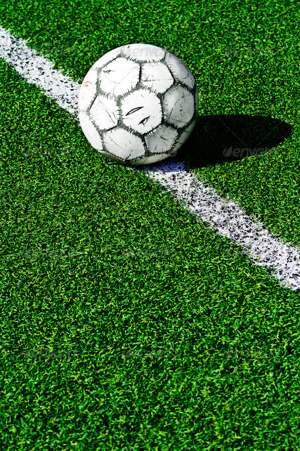 Old soccer ball on green grass - Stock Photo - Images