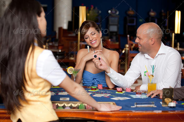 Man offering young gorgeous woman two blackjack chips  - Stock Photo - Images