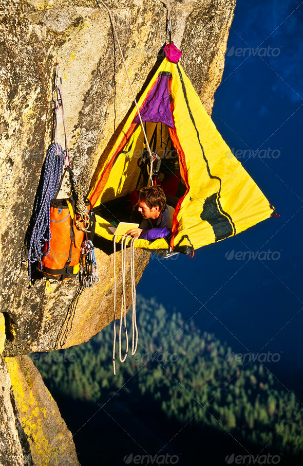 Rock climber bivouaced in a portaledge. - Stock Photo - Images