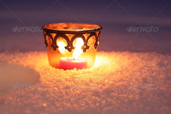 Burning candle in the snow - Stock Photo - Images