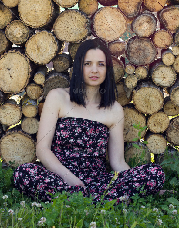 Woman sitting in front of logs - Stock Photo - Images