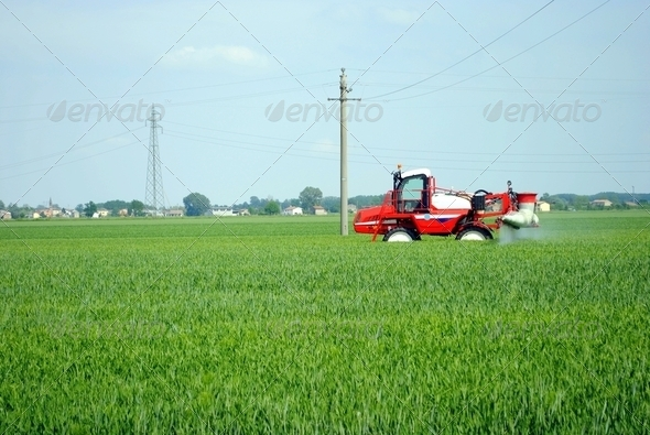 red tractor waters a cultivated field in farmlands - Stock Photo - Images