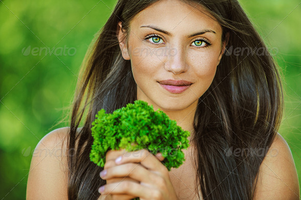 woman with bare shoulders holding bunch of parsley - Stock Photo - Images