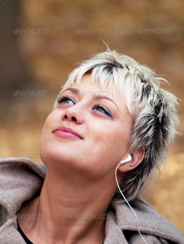 Blonde girl enjoying music in nature - Stock Photo - Images