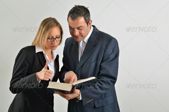 Business colleagues working together and reading a book - Stock Photo - Images