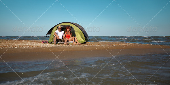 happy young couple sitting in tent seaside - Stock Photo - Images