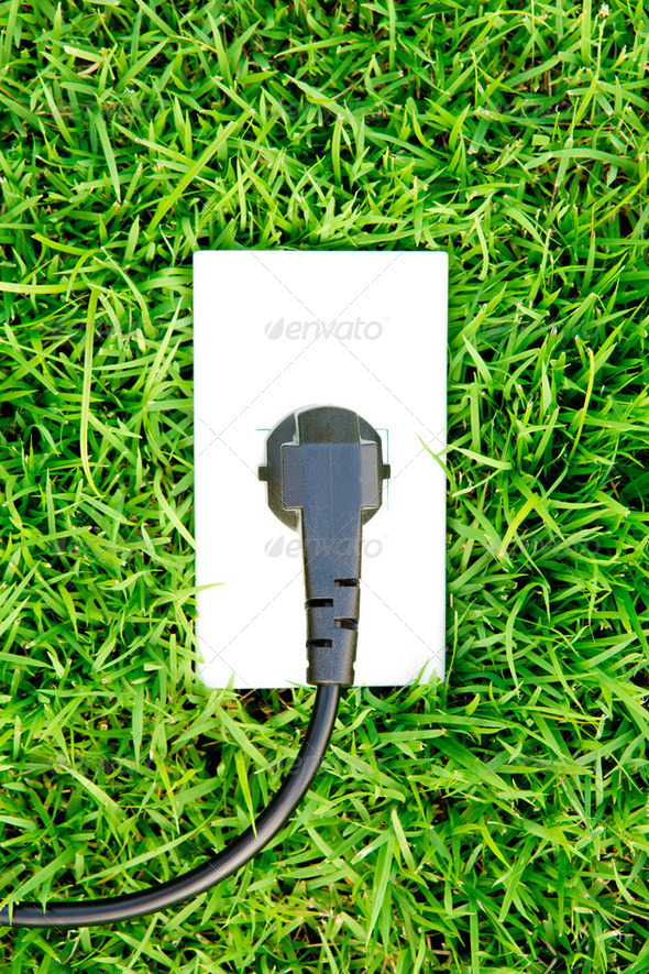 Energy concept outlet in  fresh spring green grass - Stock Photo - Images