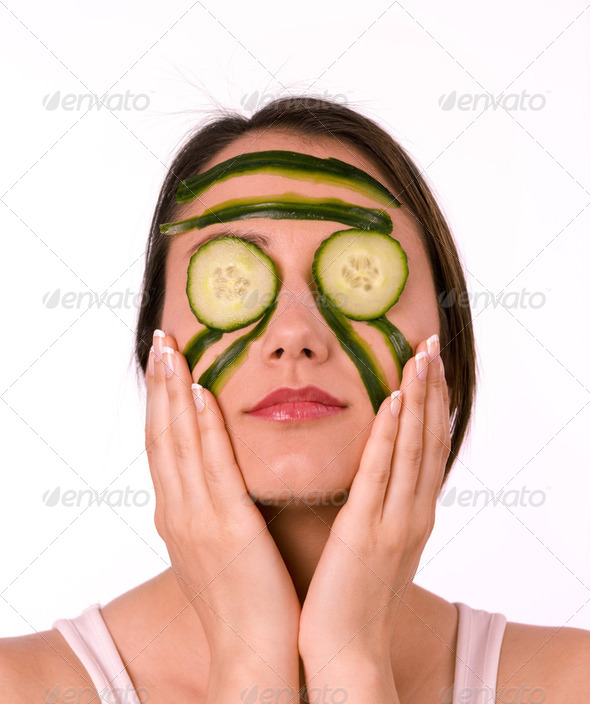 Young woman with her face covered with cucumber slices - Stock Photo - Images