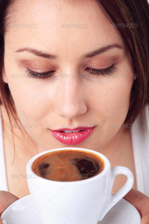 Young woman smelling a cup of coffee - Stock Photo - Images