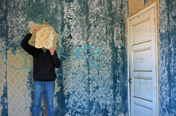 man with torn wallpaper - Stock Photo - Images