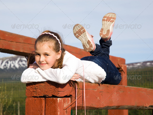 A girl lies on the balance beam and smiling - Stock Photo - Images