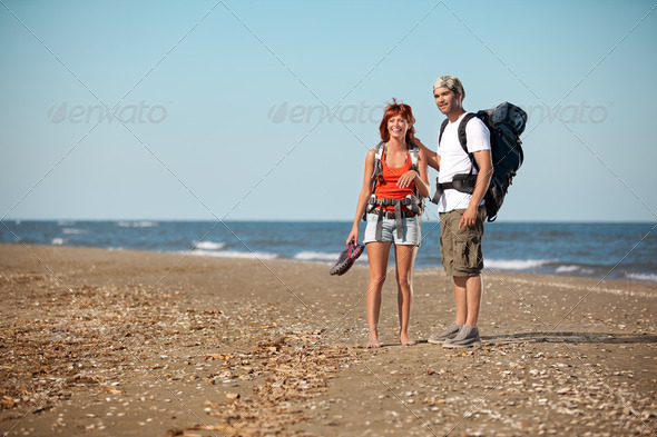 couple with backpacks walking on sea shore - Stock Photo - Images