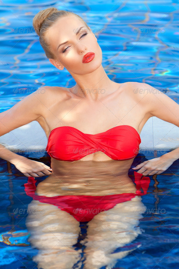 Pretty woman in a red bikini slightly upset - Stock Photo - Images