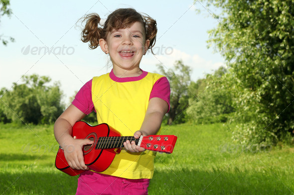 Happy little girl play guitar - Stock Photo - Images