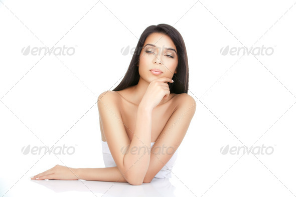 a beauty portrait of a young woman with a hand to her chin - Stock Photo - Images