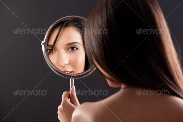a beauty image of a young woman looking into a mirror, smiling. - Stock Photo - Images