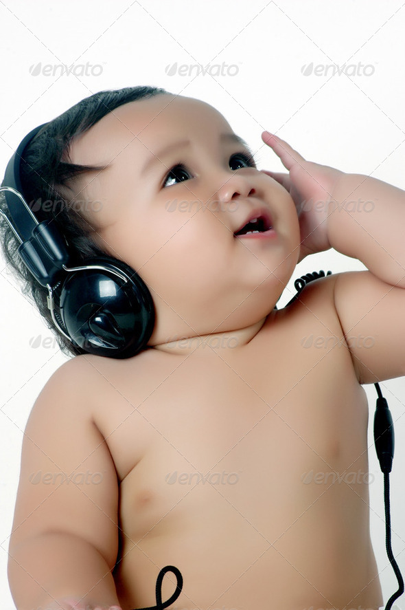 a chubby little girl listen to music with headphones - Stock Photo - Images