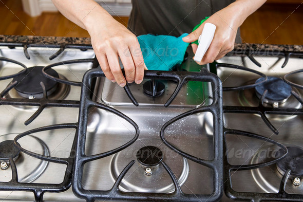 Spraying down Stove Top Range for Cleaning - Stock Photo - Images