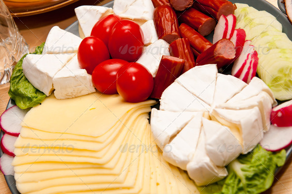 platter of cold cuts cheese and sausages with ham and tomatoes - Stock Photo - Images