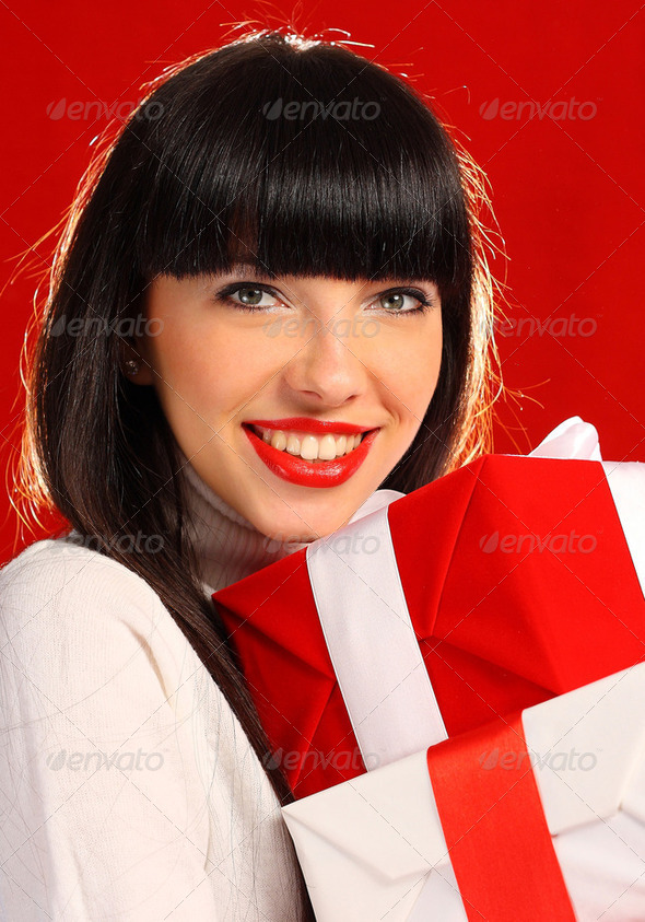 Portrait of a woman holding a few gifts - Stock Photo - Images