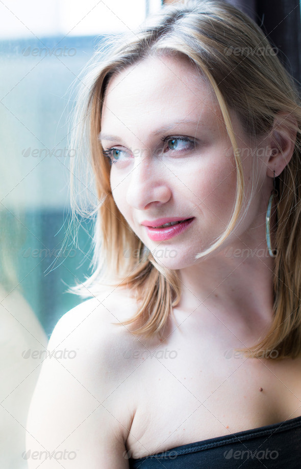 woman standing by a window looking outside - Stock Photo - Images