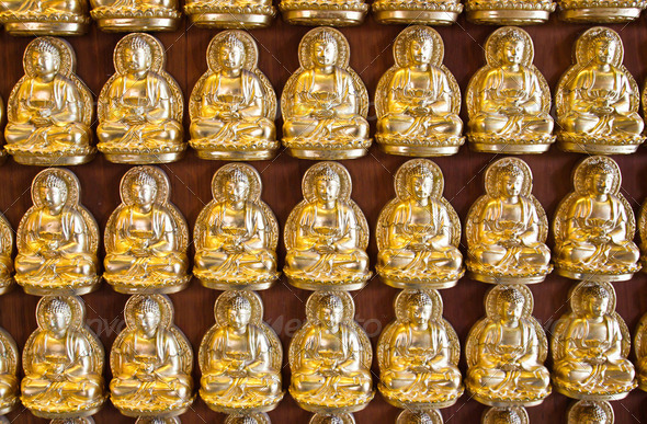 Many small Buddha statue on the wall at chinese temple, Thailand - Stock Photo - Images