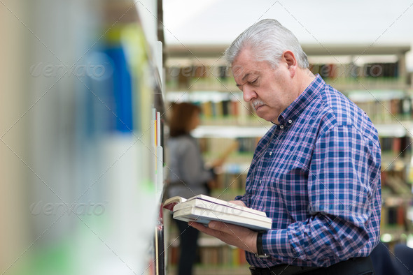 old man reading and choosing book in library - Stock Photo - Images