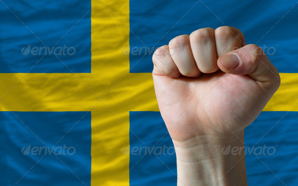 Hard fist in front of sweden flag symbolizing power - Stock Photo - Images