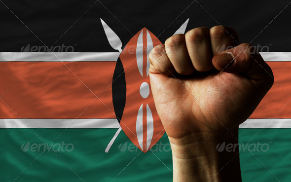Hard fist in front of kenya flag symbolizing power - Stock Photo - Images