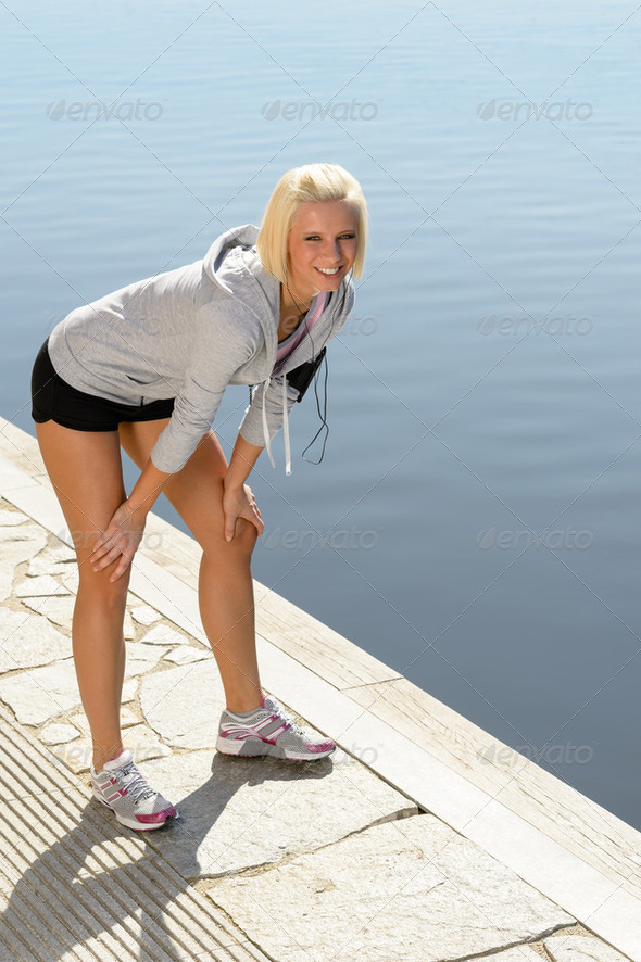 Sport woman stretching legs on a dock - Stock Photo - Images