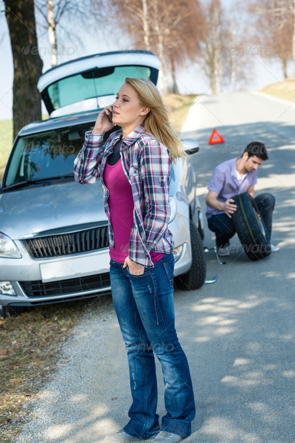 Woman calling for car assistance change wheel - Stock Photo - Images