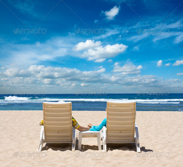 Couple in beach chairs holding hands near ocean - Stock Photo - Images