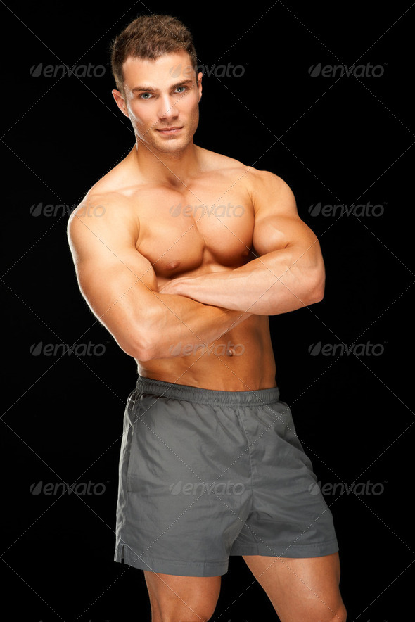 Portrait of handsome young man standing on black - Stock Photo - Images