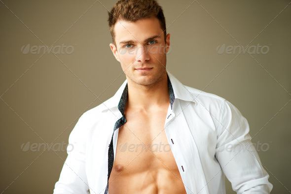 Portrait of muscular man posing in white shirt - Stock Photo - Images
