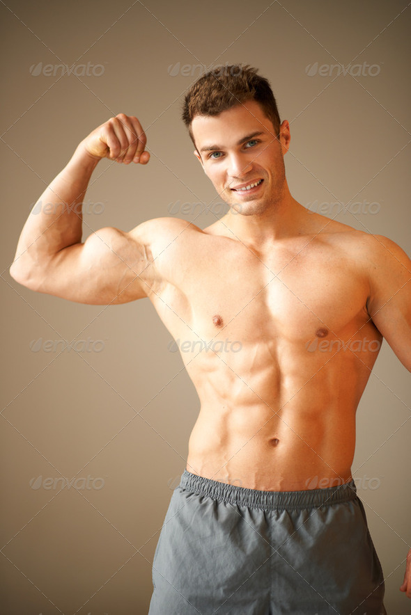 Portrait of muscular sporty man, he shows his biceps - Stock Photo - Images