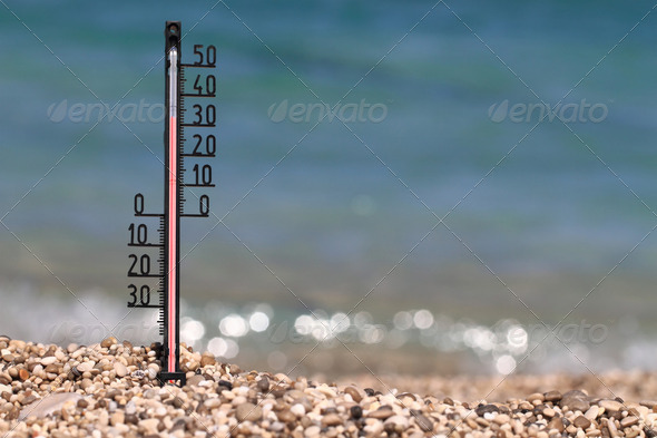 Thermometer on a beach shows high temperatures - Stock Photo - Images