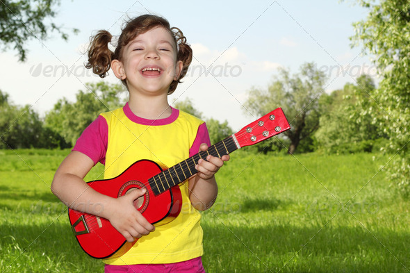 Happy little girl play guitar in park - Stock Photo - Images