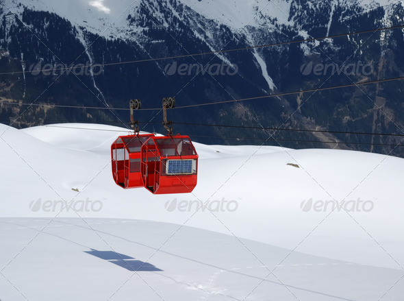 Red cabines of cable-way against black and white mountainside - Stock Photo - Images