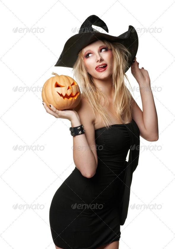 Imagen de stock de una chica vestida de bruja con calabaza de Halloween