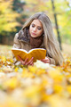 Cute young woman reading in a park in autumn - PhotoDune Item for Sale