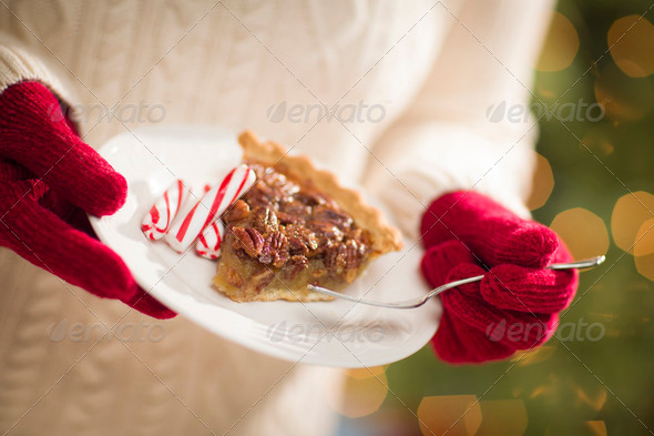 Woman Wearing A Sweater and Seasonal Red Mittens Holding A Plate of Pecan Pie with Peppermint - Stock Photo - Images
