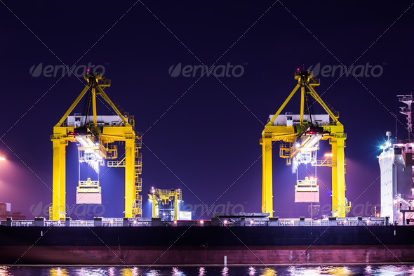 crane working with container cargo in shipyard at dusk - Stock Photo - Images
