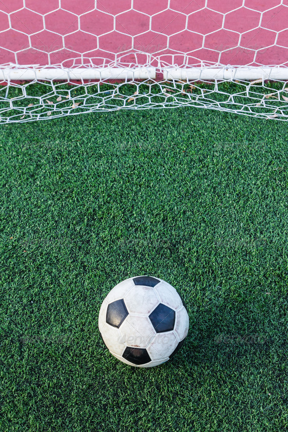 soccer ball on green grass in goal net - Stock Photo - Images