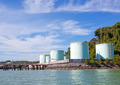 green tanks in tank farm with blue clear sky by the sea - PhotoDune Item for Sale
