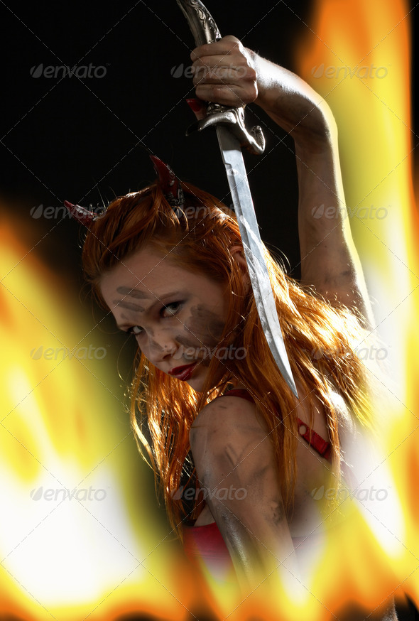 dark devil girl with a knife in fire - Stock Photo - Images